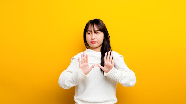 쉽게 화나게 하는 아시아 소녀 초상화 노란색 배경에서 외로운 밖을 내다보며 자신을 보호하기 위해 팔로 화난