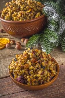 東ヨーロッパ、ロシア、ウクライナ、スラブの伝統的なクリスマス料理、甘いクティア、ドライフルーツ、ケシの実、ナッツ。クリスマスツリーの枝と木製の背景