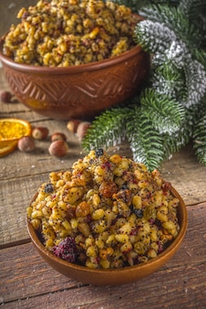 East european, russian, ukrainian, slavic traditional christmas food, sweet kutya, with dried fruits, poppy seed and nuts. wooden background with christmas tree branches