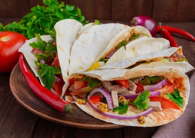 さまざまな具材(肉、サラミ、卵、きゅうり、パセリ、トマト、唐辛子、ディジョンマスタード)を添えたイーストピタパン。タコス。