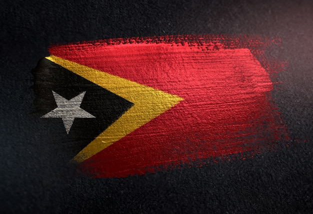 East timor flag made of metallic brush paint on grunge dark wall