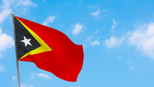 Флаг восточного тимора на шесте. голубое небо. государственный флаг восточного тимора