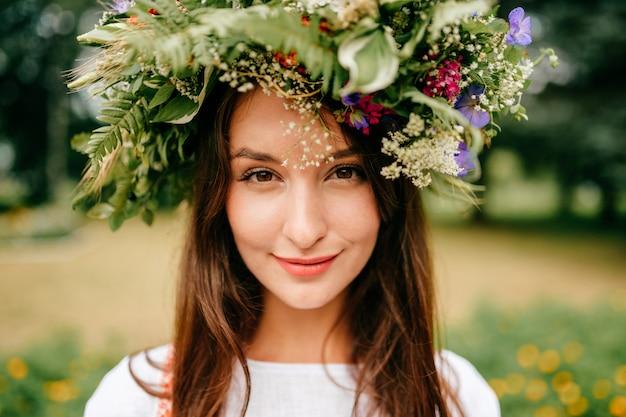 夏の花の花輪を持つ伝統的なスラブドレスの美しい少女のクローズアップの肖像画。花のeast宴で夏の民族民族スタイルの陽気な女性。