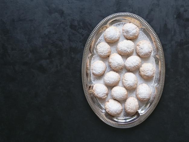 黒いテーブルの上のラマダンのお菓子。エジプトのクッキー「カフエルイード」-エルフィトルイスラムのeast宴のクッキー。トップビュー、コピースペースの背景