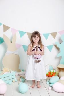 부활절! 하얀 드레스를 입고 아름 다운 소녀는 부활절 토끼를 포옹입니다. 많은 다른 다채로운 부활절 달걀, 화려한 인테리어. 가족 휴가. 부활절 인테리어. 농업. 어린이와 정원.