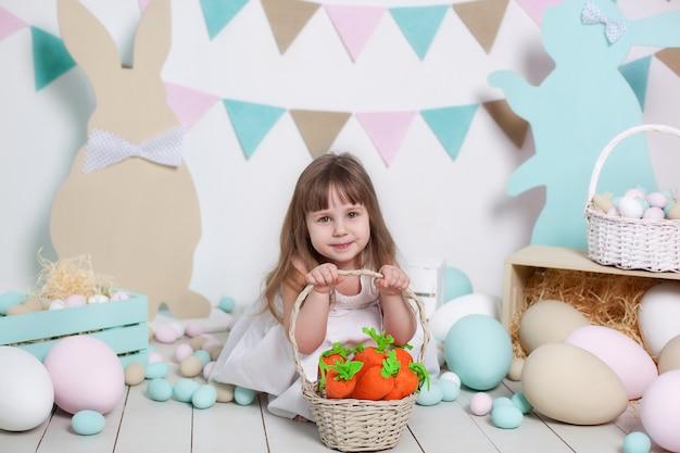 부활절! 하얀 드레스를 입고 아름 다운 소녀는 부활절 바구니와 당근 앉아있다. 토끼, 다채로운 부활절 달걀. 부활절 인테리어. 가족 축하. 농업. 어린이와 정원.