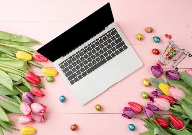 부활절과 봄 개념. 분홍색 나무 배경에 노트북 컴퓨터, 화려한 튤립과 부활절 달걀의 상위 뷰