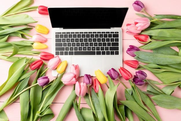 부활절과 봄 개념. 핑크 나무 배경에 튤립 꽃으로 장식 된 노트북 컴퓨터의 상위 뷰