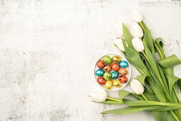 イースターと春のコンセプト。コンクリートの背景に白いチューリップと色付きのイースターエッグの上面図