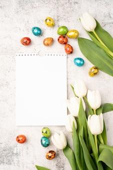 イースターと春のコンセプト。コピースペースのあるコンクリートの背景に白いチューリップ、空白のカレンダー、色付きのイースターエッグの上面図