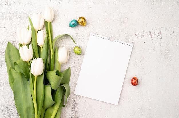 イースターと春のコンセプト。コンクリートの背景に白いチューリップ、空白のカレンダー、色付きのイースターエッグの上面図
