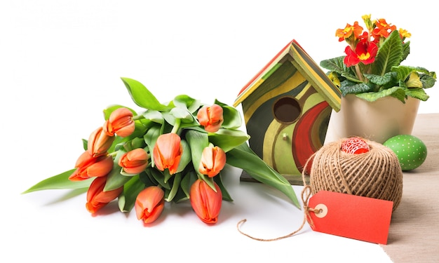 Easter arrangement with orange flowers on whte