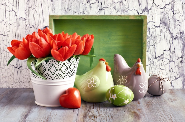 Easter arrangement with orange tulips, ceramic hens and eggs