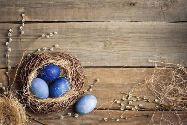 イースターの背景。木製のテーブル、コピースペースのわらと柳の枝の巣の青い卵