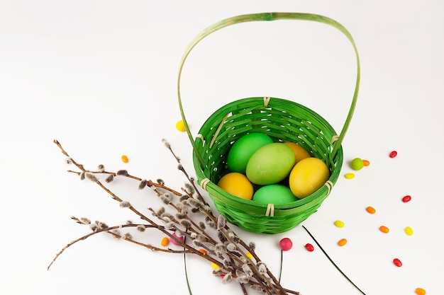 Easter background, colorful easter eggs and decorations next to baskets and pussy willow branches