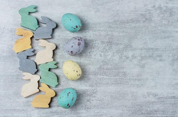 イースターの背景カラフルなパステルカラーのイースターエッグと小さなかわいい木製のウサギ