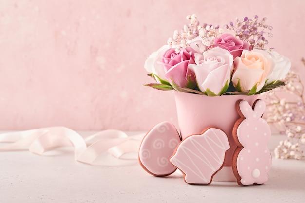 꽃병, 부활절 달걀, 토끼 및 병아리에 분홍색 배경 테이블에 아름다운 꽃다발 핑크 장미 꽃과 부활절 배경 장식. 복사 공간 부활절 개념입니다.