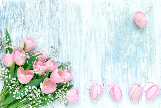 Easter background. decorative easter pink eggs and pink tulips on blue background. copy space, top
