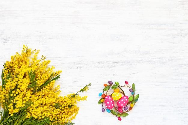 Пасхальный фон. пасхальное украшение и букет мимозы на белом фоне. вид сверху, копия пространства.