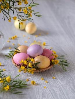 イースターの背景。木製のテーブルに黄色い花で飾られた卵