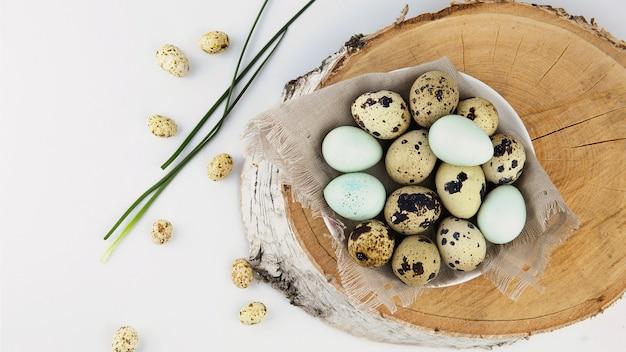 イースターの背景、黄麻布の卵は明るい背景の木のカットの上に立っています