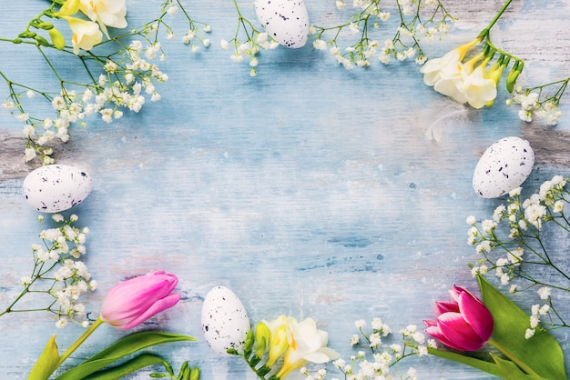 Easter background. a frame of spring flowers and easter eggs. copy space.