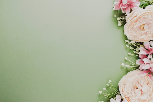 Easter background frame with flowers on green board. festive frame or border.