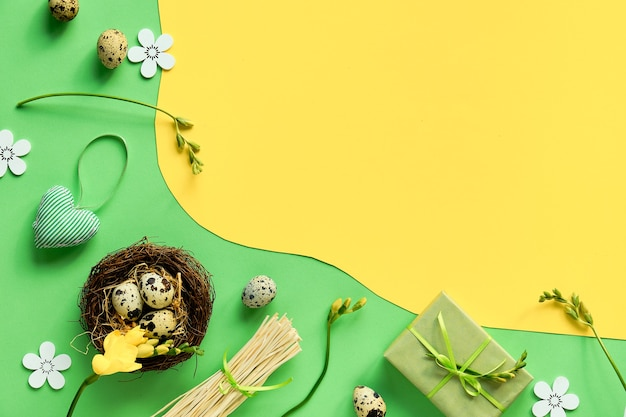 Easter background in green and yellow. top view on bird nest with quail eggs, gift box, soft heart toy and freesia flowers.