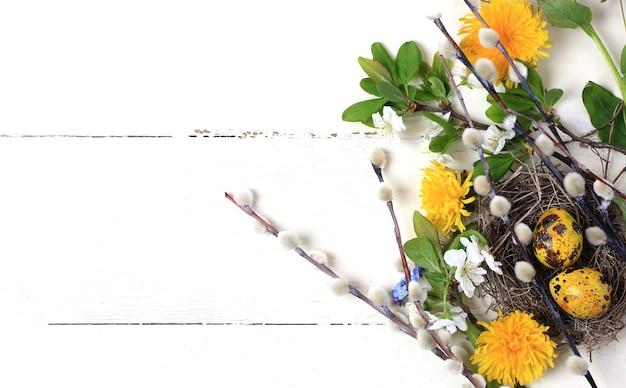 흰색 나무 배경 위에 그려진 달걀 버드나무 꽃 민들레가 있는 부활절 배경 둥지