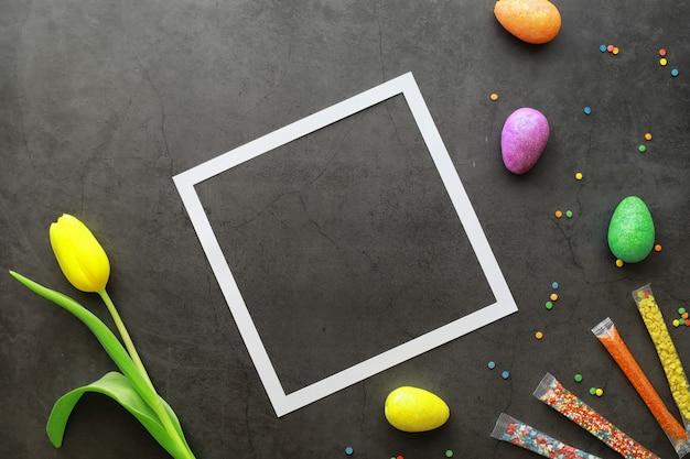 검은 돌에 부활절 배경입니다. 여러 가지 빛깔의 계란과 과자. 튤립 꽃다발입니다.