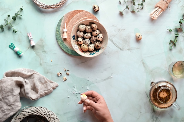 ミントグリーンの大理石のテーブルのイースターの背景。ウズラのイースターエッグと天然温泉の装飾とユーカリの小枝。ガラスのティーポットの緑茶。