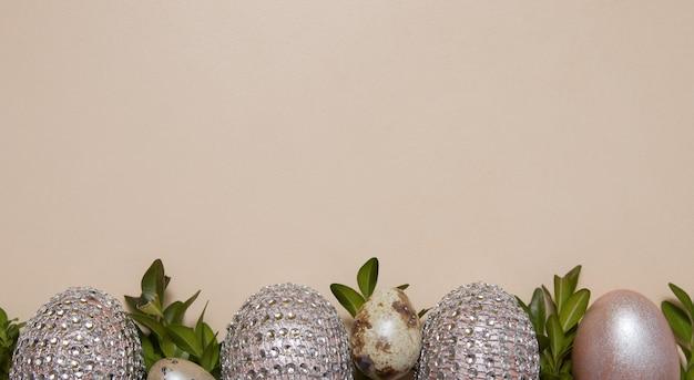 Пасхальный фон вид сверху блестящие яйца и листья на бежевом