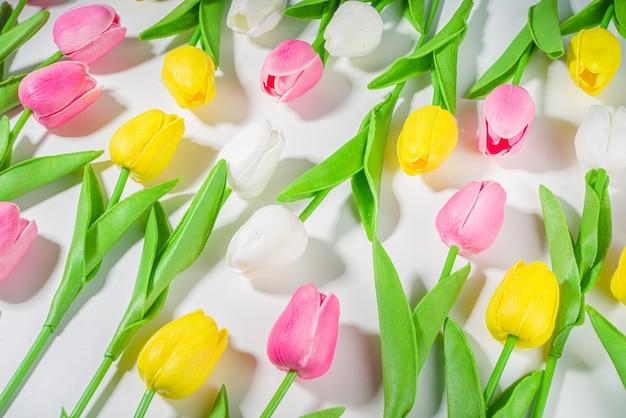 イースターの背景のチューリップの花束、白いテーブルの背景の上の大きなカラフルなチューリップの花の花束トップビューテキストのコピースペース。春休みの花柄