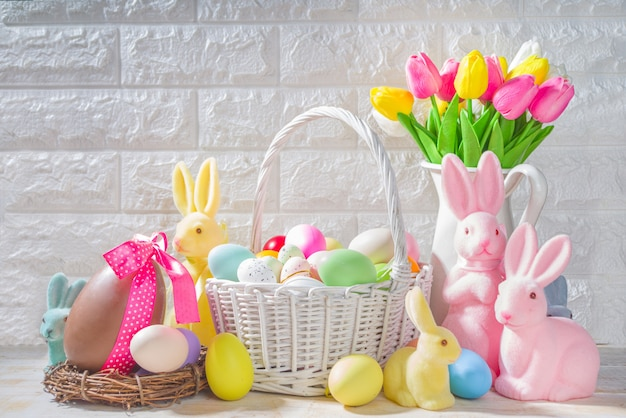 イースターの背景。チューリップの花の花束、イースターエッグ、ウサギのウサギの装飾が施された花瓶。白い木の台所のテーブルの背景のコピースペースに