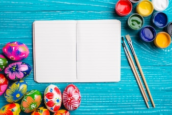 Easter background with blank notebook and paint brushes
