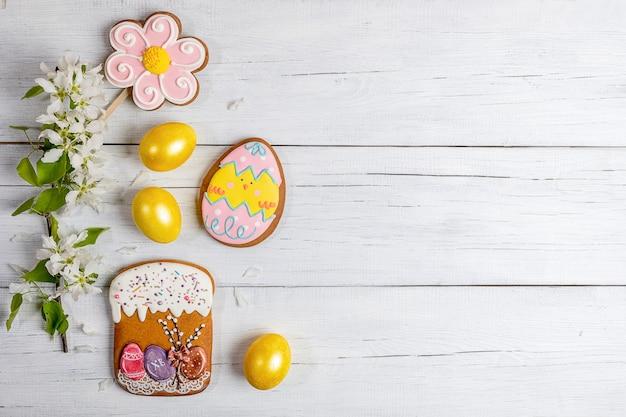 ブルーミングアップルツリーブランチ、黄色の卵、白い木製のテーブルにジンジャーブレッドとイースターの背景。