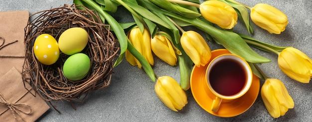 Предпосылка пасхи с голубыми, зелеными яйцами и чашкой чая в гнезде и желтых тюльпанах. вид сверху с копией пространства.