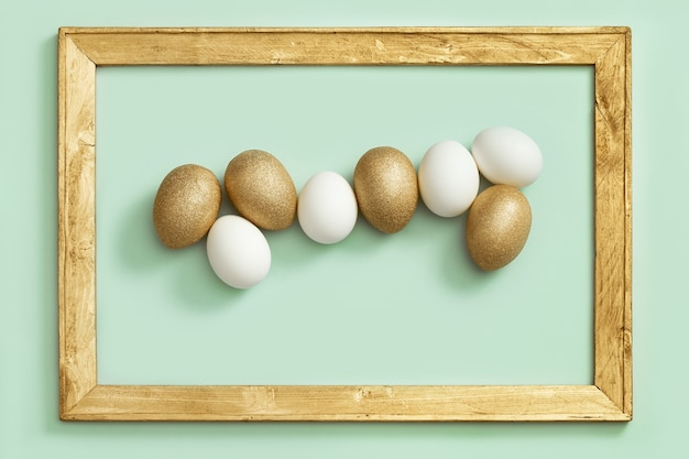 Easter background with bright eggs, shiny golden colored and white eggs on green paper in wooden frame