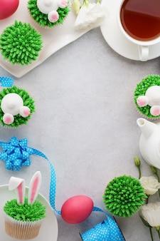 バニーカップケーキ、お茶、塗られた卵とイースターの背景。