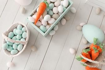 白い木の上にカラフルな卵と黄色のオレンジのニンジンとイースターの背景。