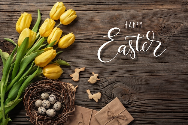 Easter background with colorful eggs and yellow tulips on wooden table, top view