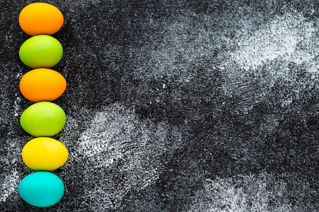 Easter background with copy space. paschal mockup with painted eggs on grunge black shabby board. concrete surface, creative modern design.