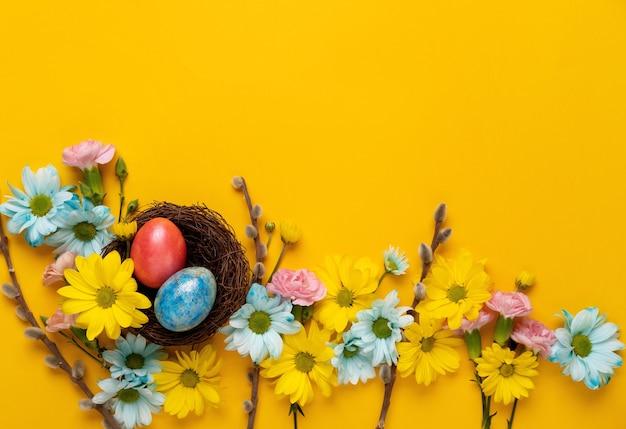 부활절 달걀과 봄 꽃과 부활절 배경입니다. 평평하다. 인사말 카드 템플릿입니다.