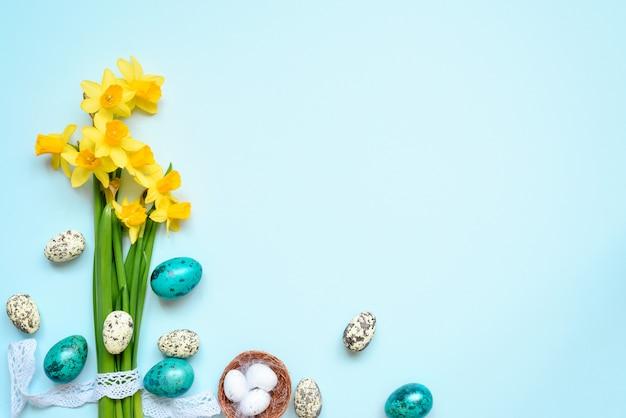 イースターエッグと青の背景に春の花とイースターの背景。上面図