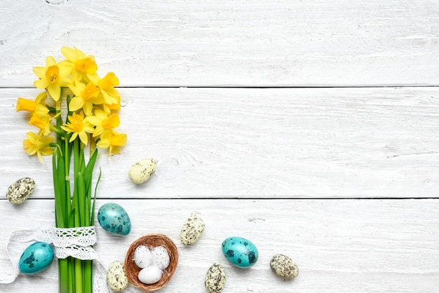 イースターの背景にイースターエッグ、白い木製のテーブルの春の花