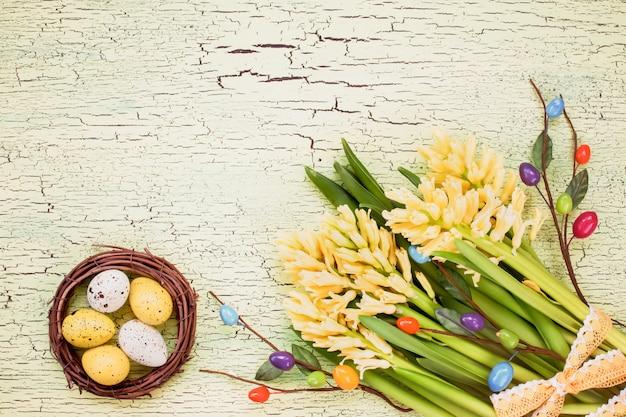 イースターエッグと黄色い花を持つイースターの背景。コピースペース、トップビュー
