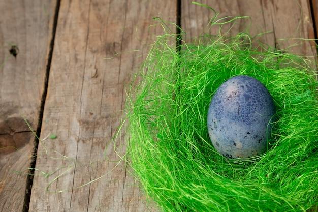 나무 테이블에 녹색 둥지에 부활절 달걀과 부활절 배경