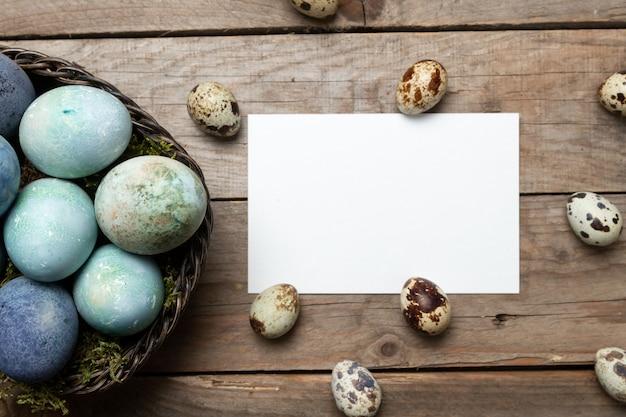 巣の中のイースターエッグと木製のテーブルのテキスト用の紙のシートとイースターの背景。