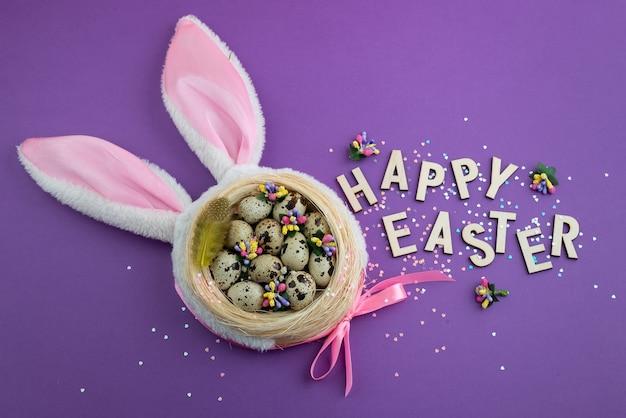 紫色の背景に卵とおもちゃのウサギの耳とイースターの背景