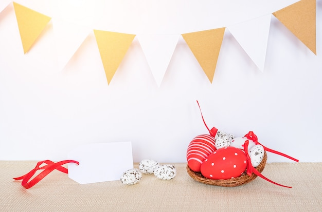 Easter background with eggs in bird nest and empty gift tag sign for happy easter greeting message